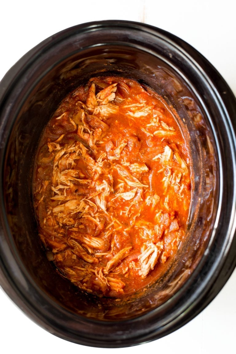 Shredded chicken with enchilada sauce in a black slow cooker pot