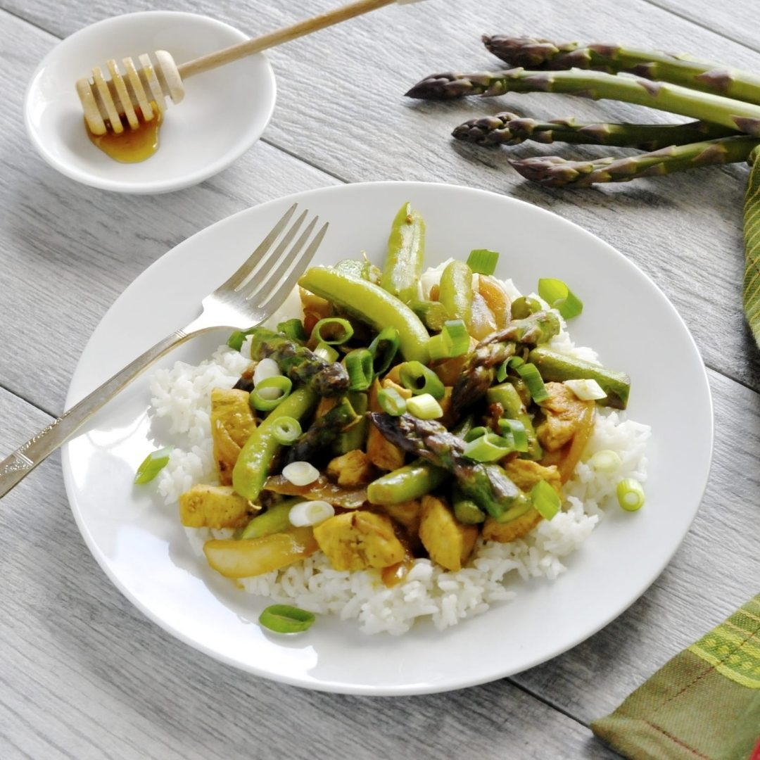 white plate with honey mustard chicken stir fry on top and asparagus set on table