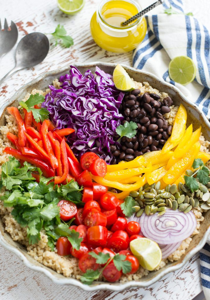 large bowl filled with colorful salad on white table with striped blue napkin and a side of dressing in small jar