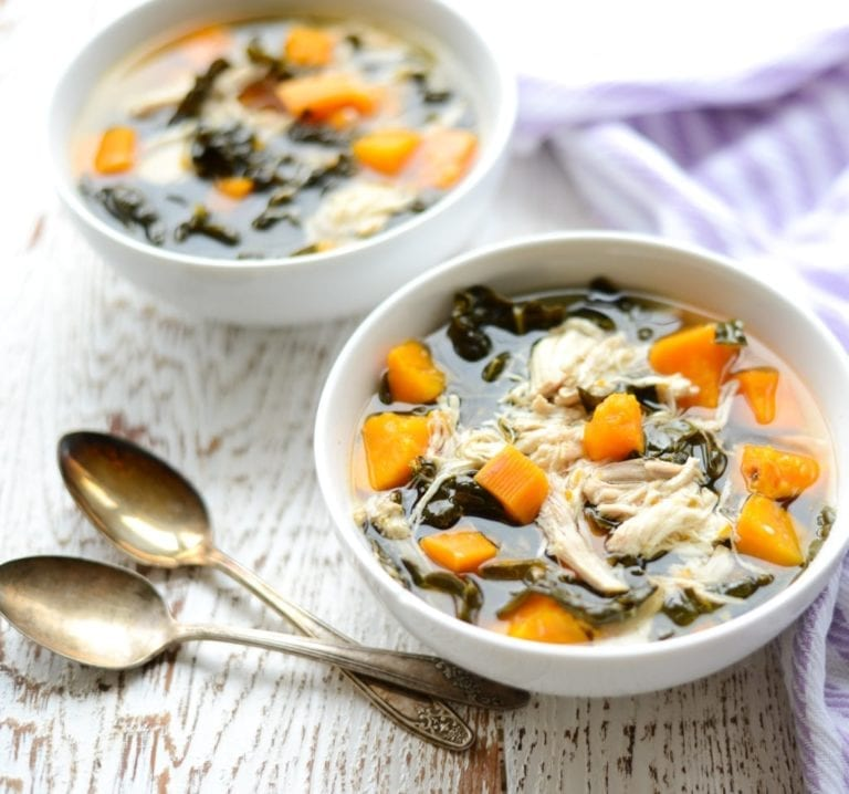 two white bowls of slow cooker chicken kale and sweet potato soup with spoons on white table