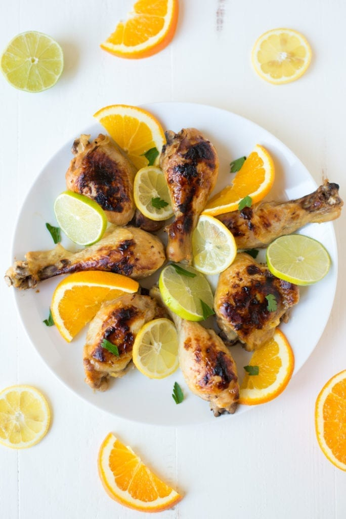 white plate with chicken and citrus slices on white table