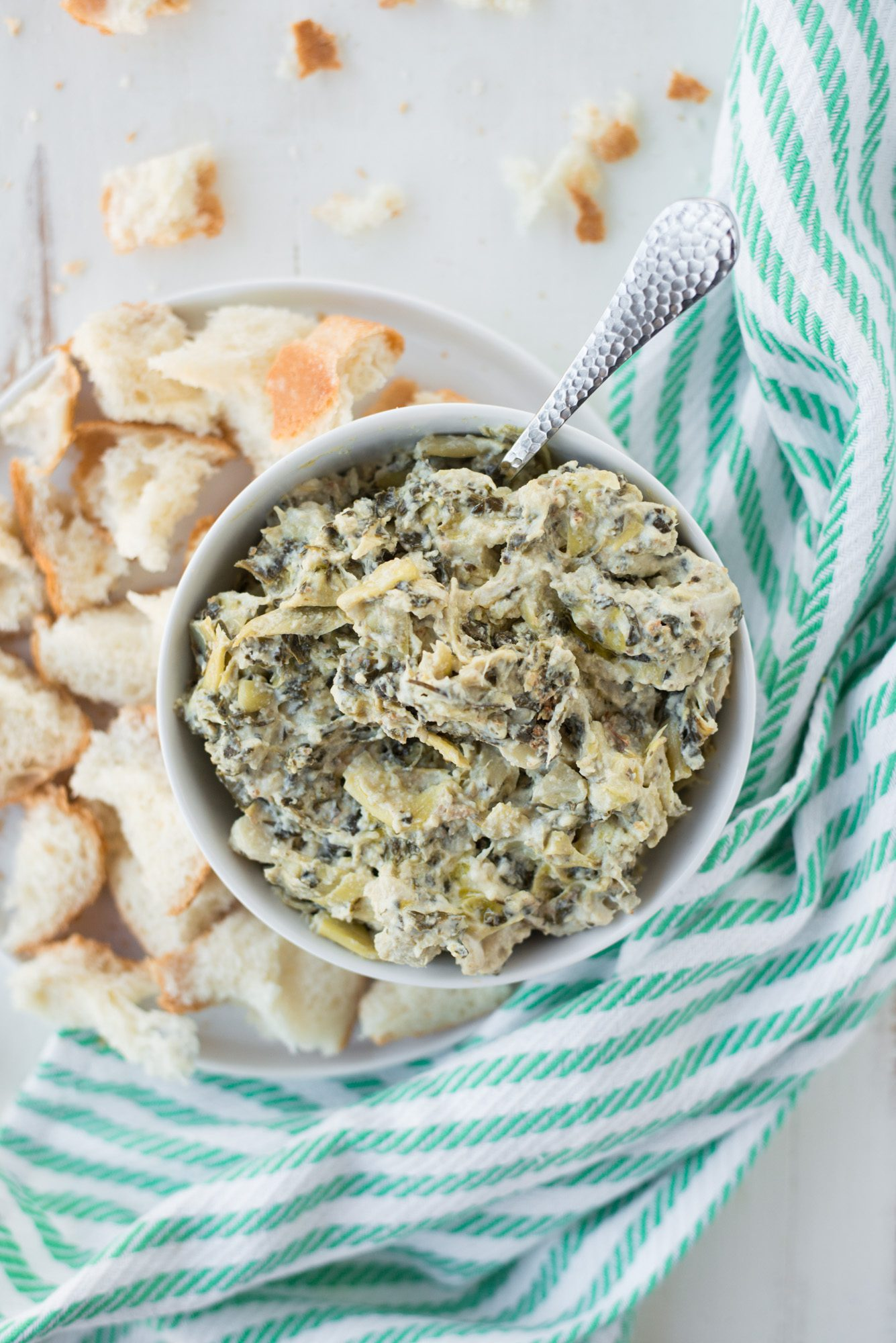 bowl of artichoke dip with bread on white plate with striped napkin