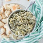 bowl of artichoke dip with a spoon, bread pieces and striped napkin