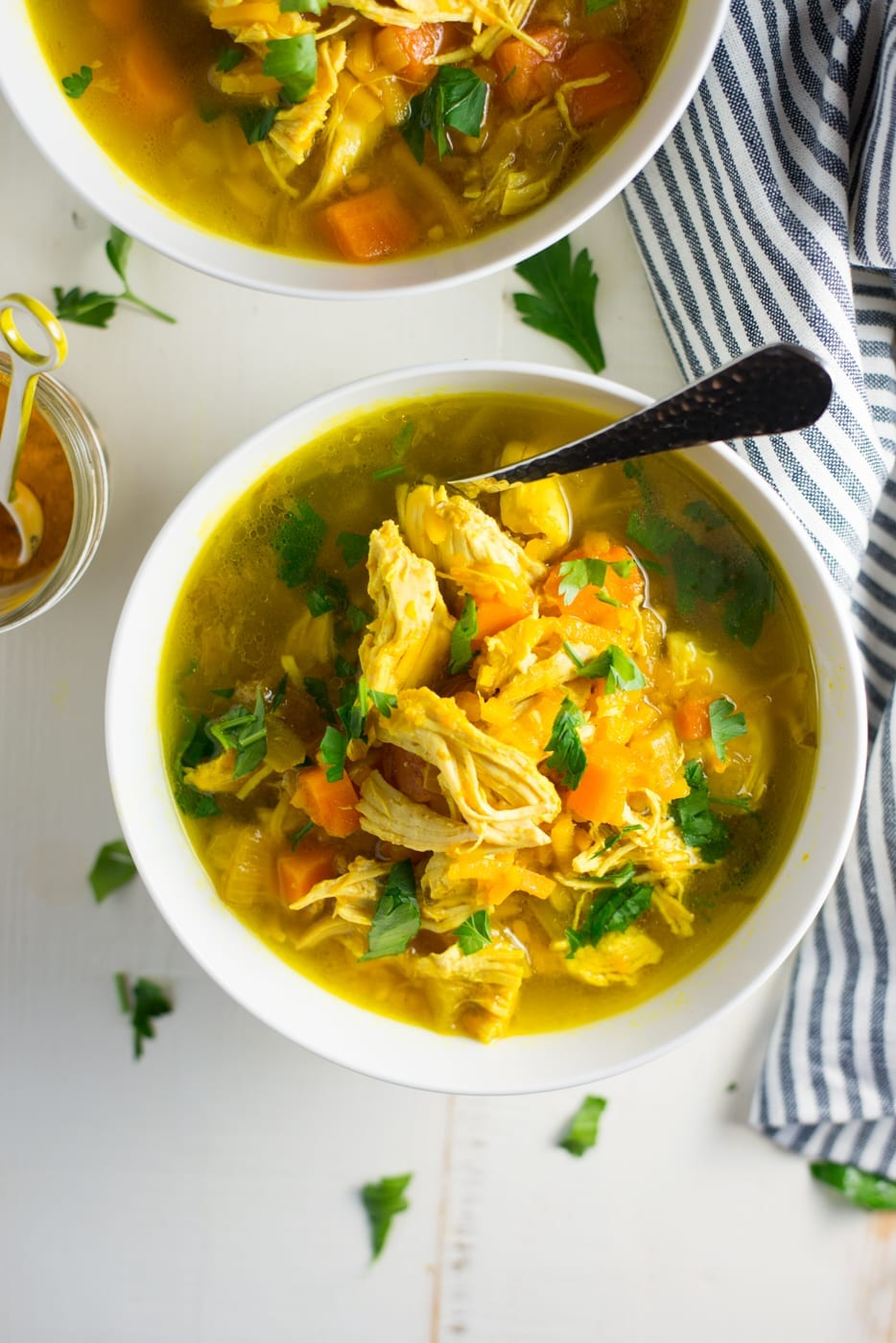 two white bowls of instant pot turmeric chicken soup with herbs and striped napkin