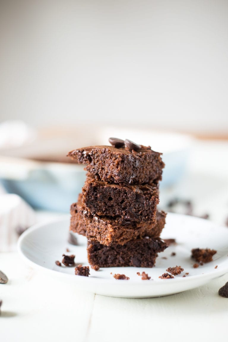 stack of four brownies on a white plate and white wood table