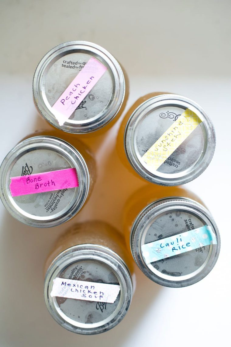 five mason jars with metal lids and taped labels with recipe names