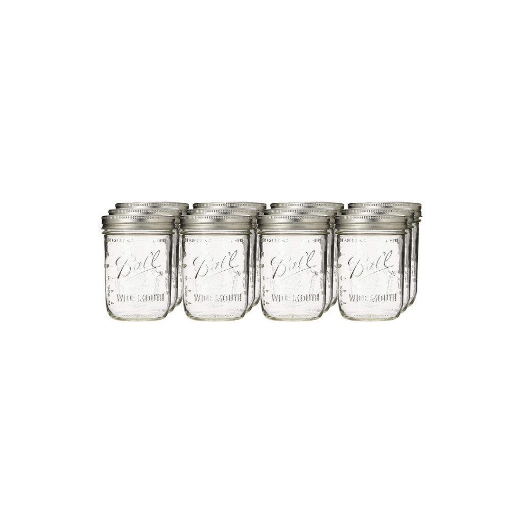 set of twelve clear glass wide mouth mason jars with metal lids on white background