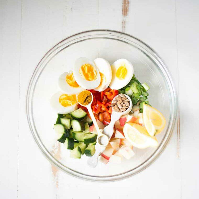 Top down shot of hard boiled eggs, cucumber, lemon, and red pepper in a glass bowl