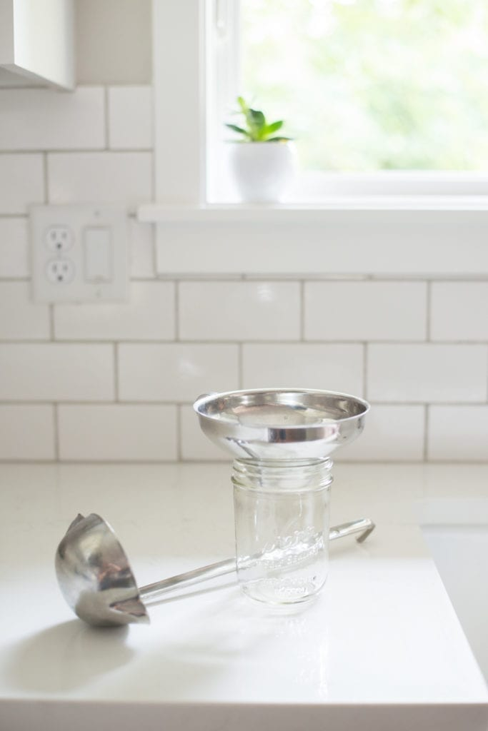 small glass mason jar with ladle and funnel on white countertop