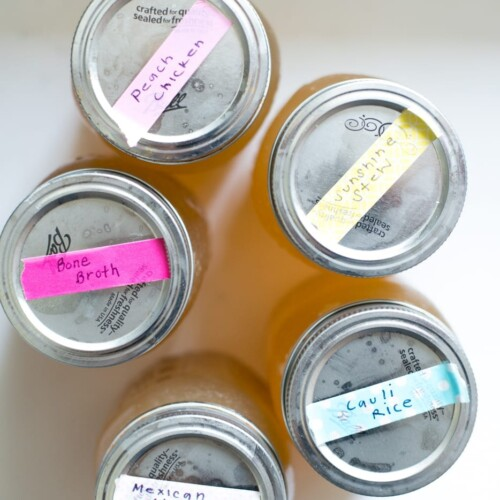 five mason jars with metal lids and taped labels