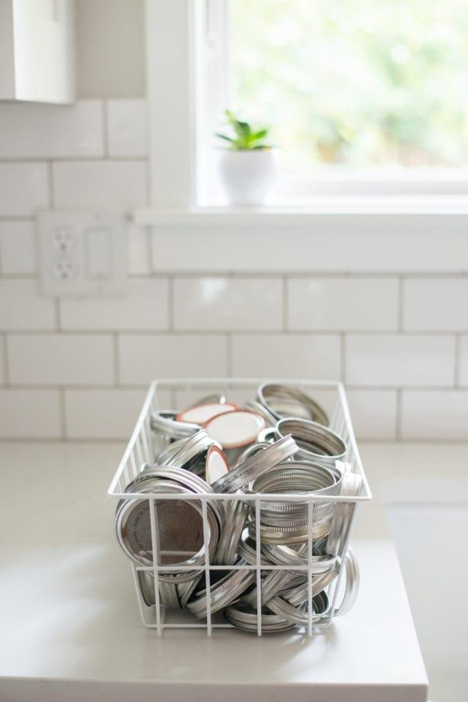 white basket filled with metal jar lids on white kitchen countertop