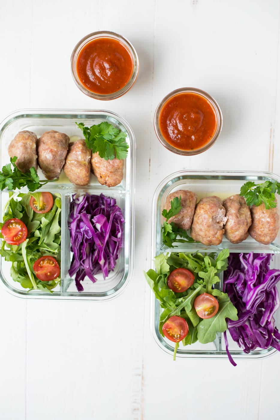 5-ingredient meatballs in glass meal prep containers with cabbage and arugula on white background