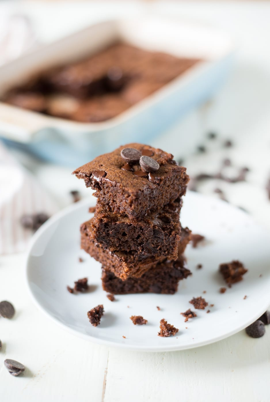 four brownies stacked on top of each other on a white plate with a pan of brownies in the background