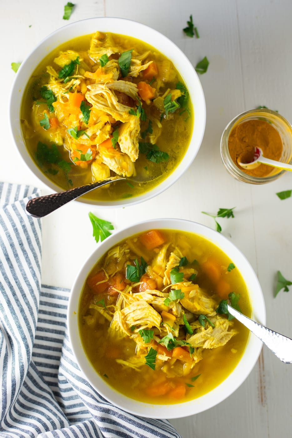 two bowls of chicken noodle soup with fresh herbs on top on white table