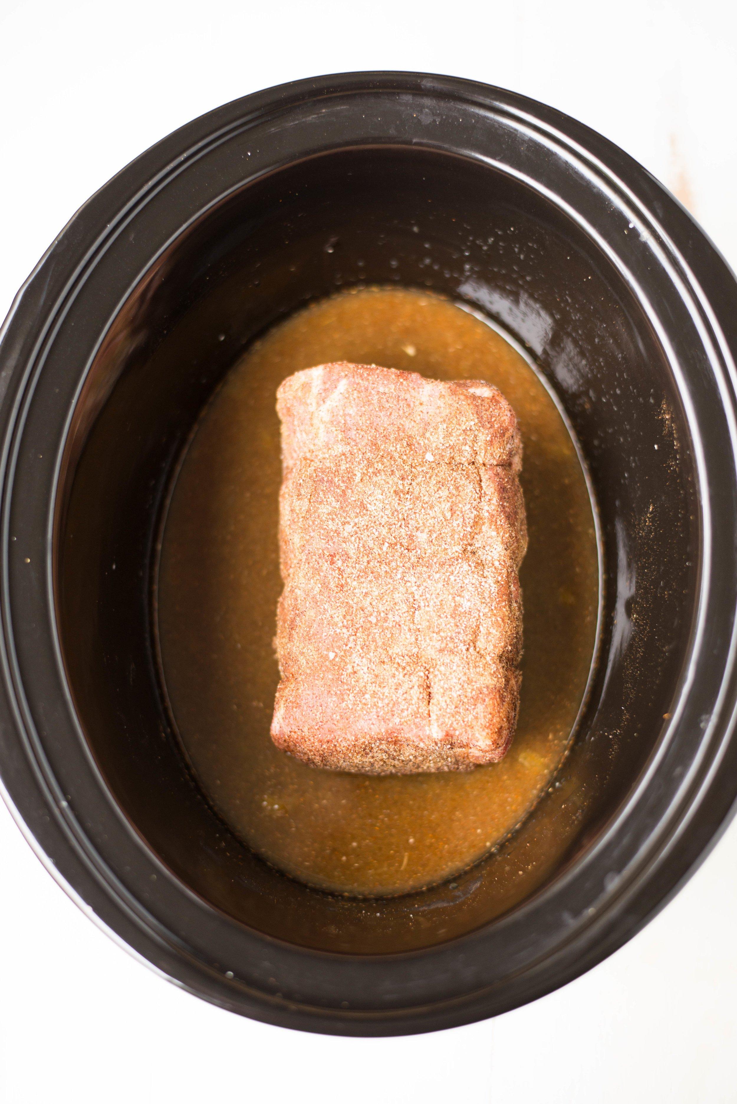 pork shoulder in black slow cooker with orange juice and spices
