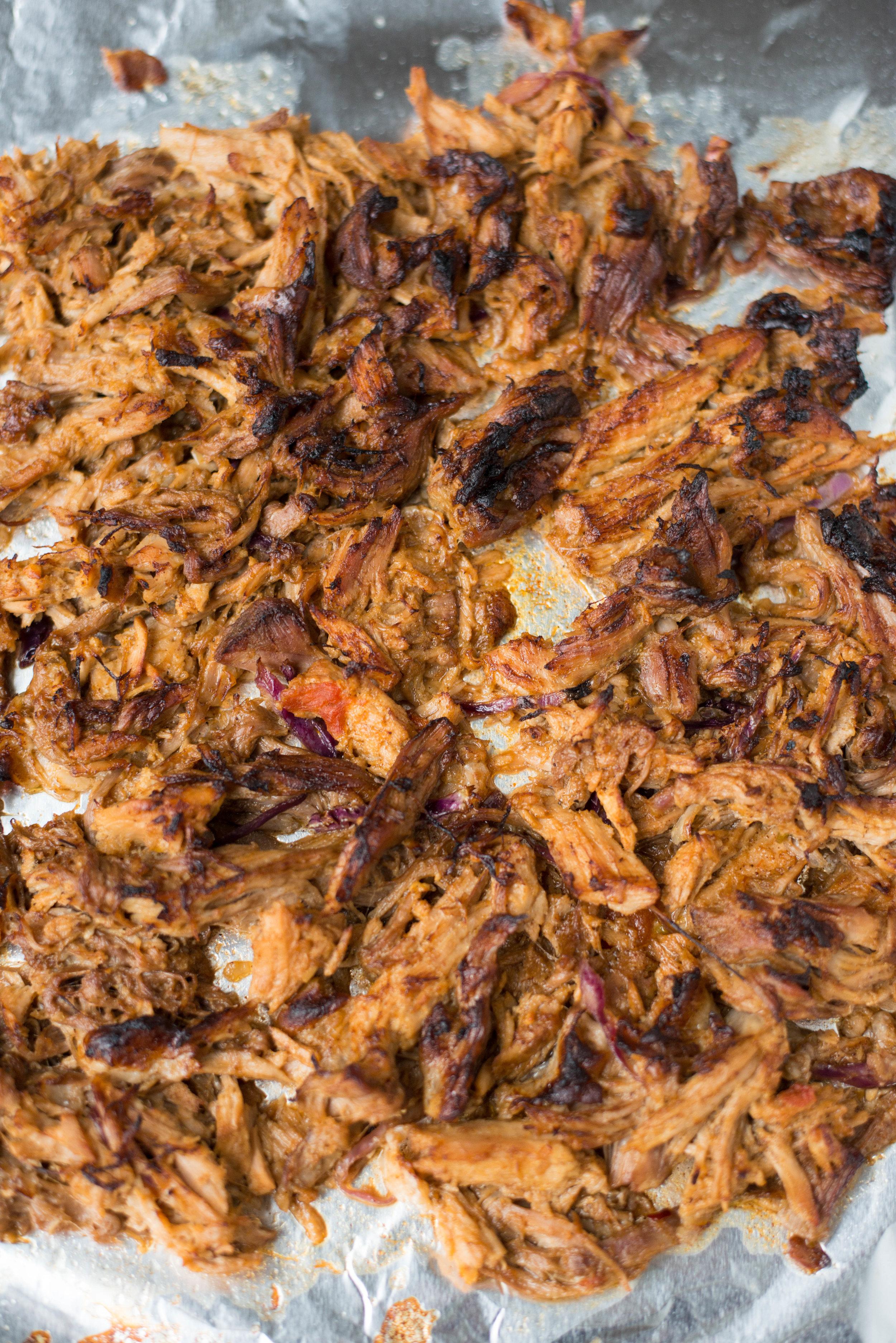 crispy shredded pork carnitas on foil lined baking sheet