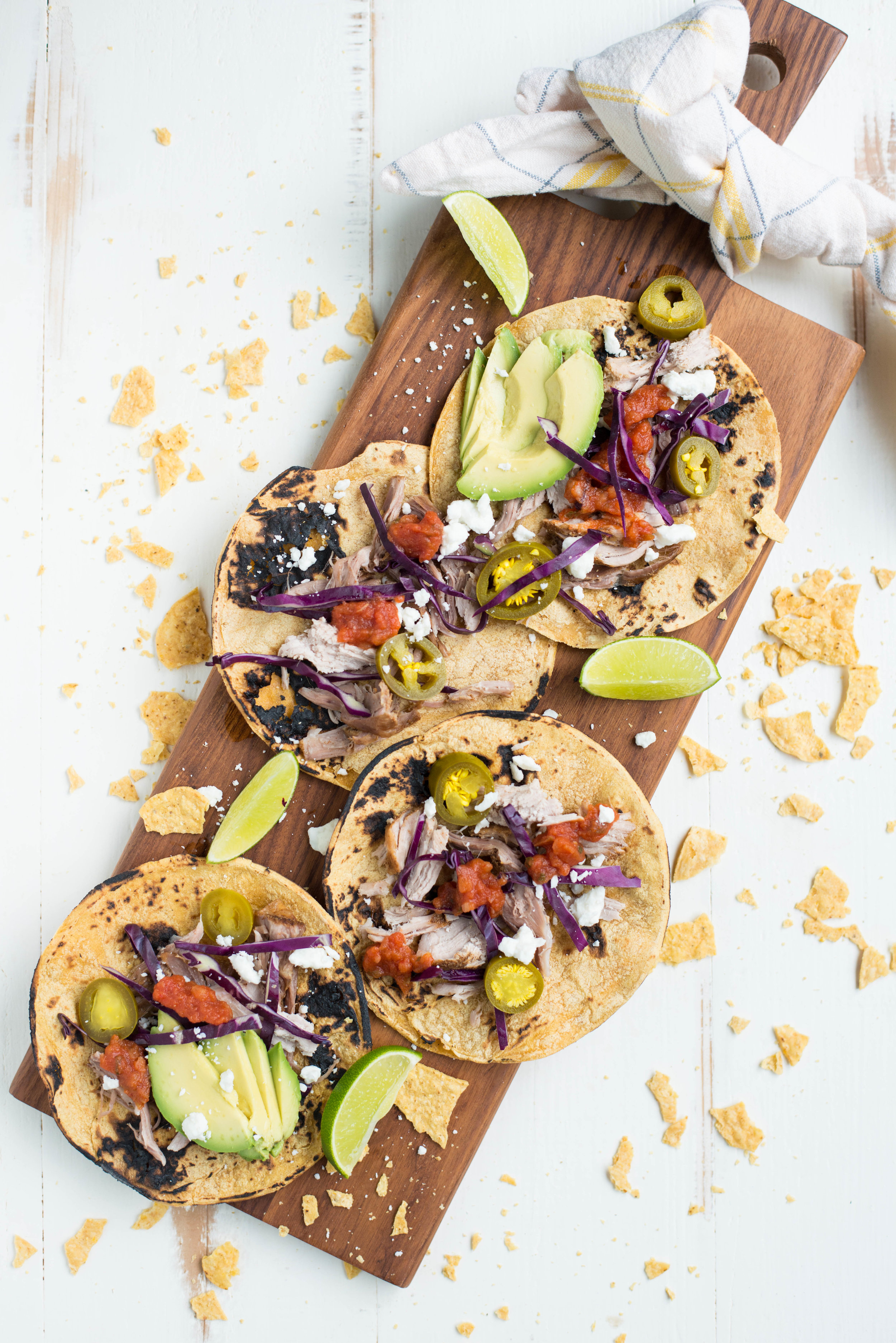 corn carnitas tacos on wood board with tortillas chips on white table