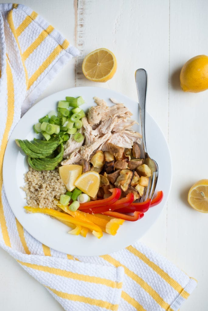 white plate with chicken and vegetables on white table with striped napkin