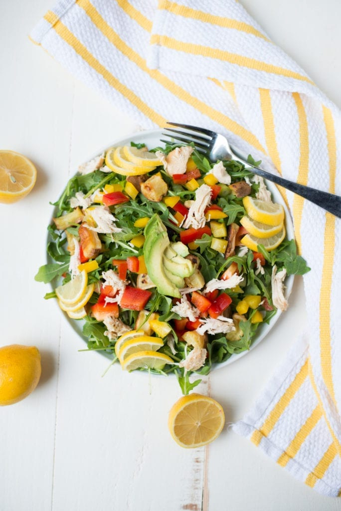 salad on white plate with lemon slices and striped napkin on white table