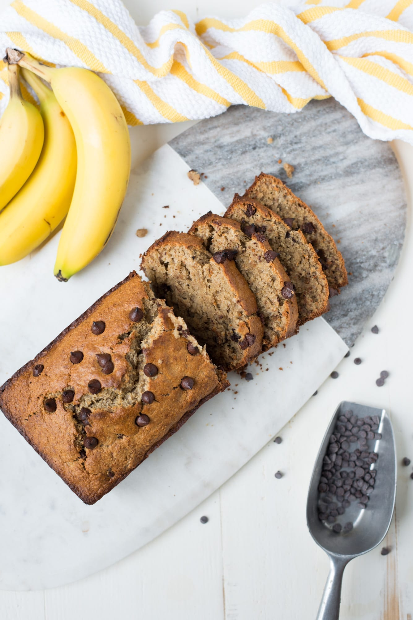 loaf of banana bread with slices on a marble cutting board with bananas and striped napkin and scoop with chocolate chips