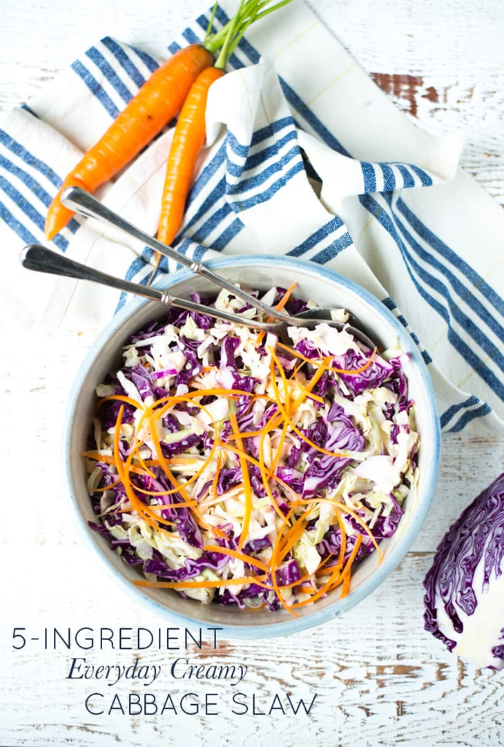 thinly sliced cabbage and carrots in a bowl with striped blue napkin