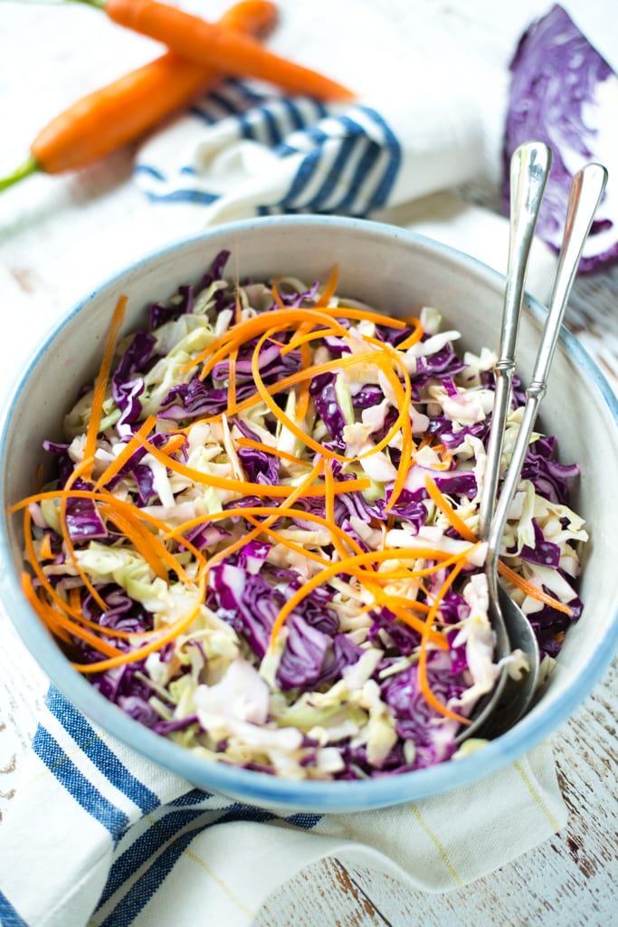 thinly sliced cabbage in a white bowl with striped blue napkin and carrot on table
