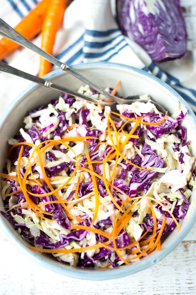 thinly sliced cabbage and carrots in a bowl with striped blue napkin and two spoons