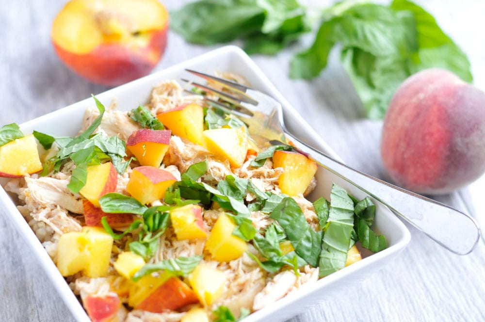 slow cooker peach chicken with basil in a white square bowl with fork on gray table