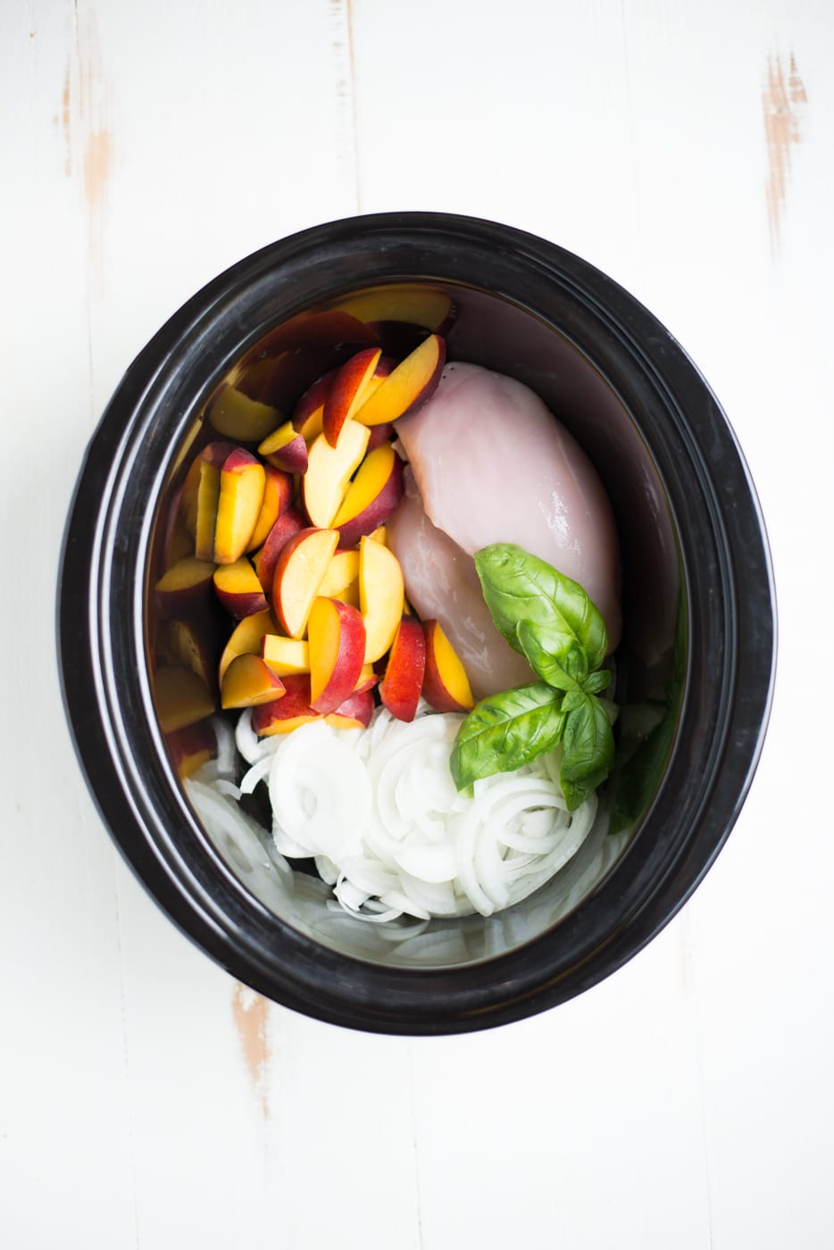 black slow cooker with sliced peaches and chicken and onions and basil on white background