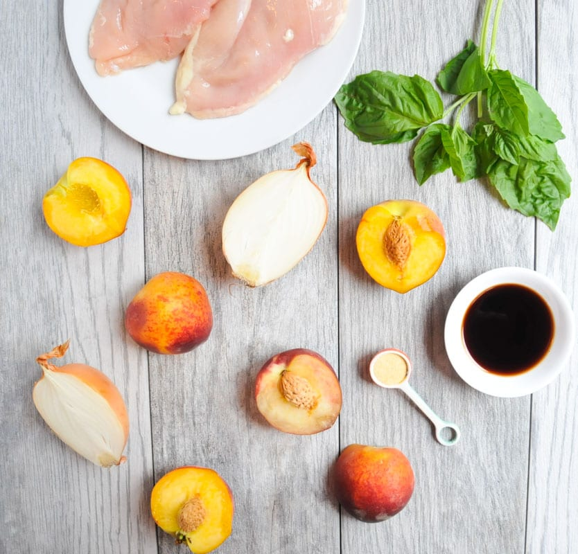 gray table with peach halves and onions and basil and raw chicken breasts