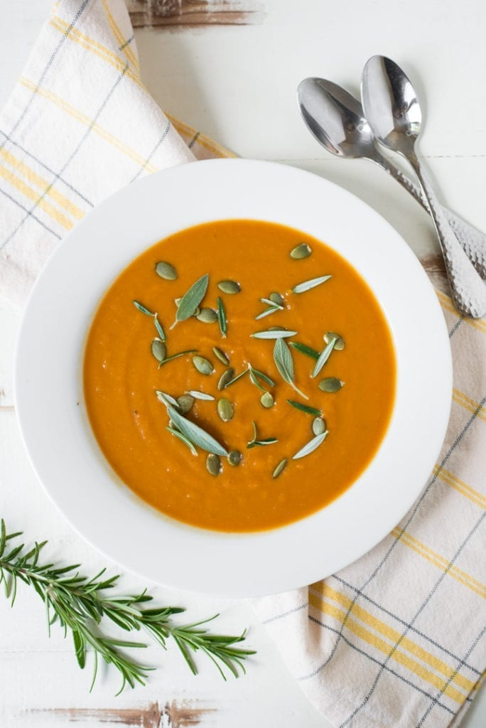 pumpkin soup in white bowl with herbs and spoon