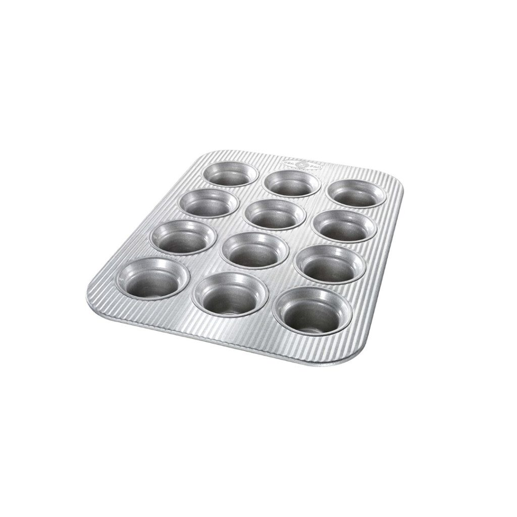 silver muffin tin on white background