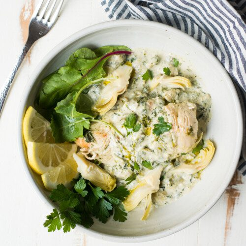 chicken dish with spinach and sliced lemon in bowl with striped napkin on white table with a fork