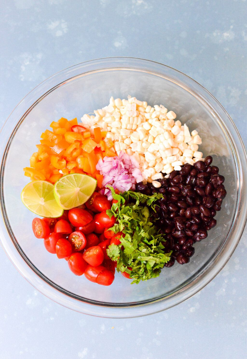 ingredients for black bean salad with corn in glass mixing bowl