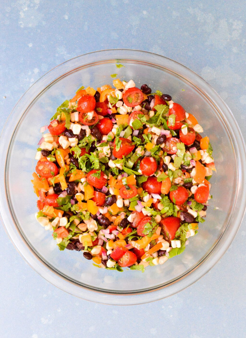 ingredients for black bean salad with corn mixed together in glass mixing bowl
