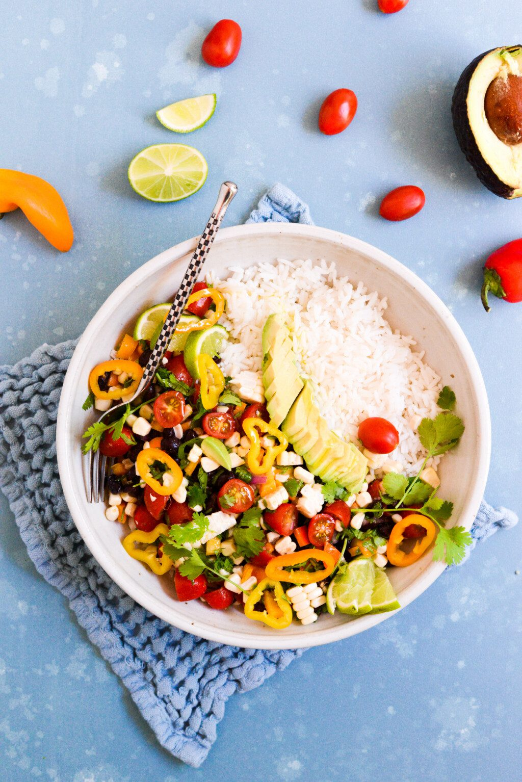 black bean salad in white bowl with rice on blue background