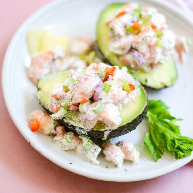 close up of two shrimp stuffed avocado halves on a white plate