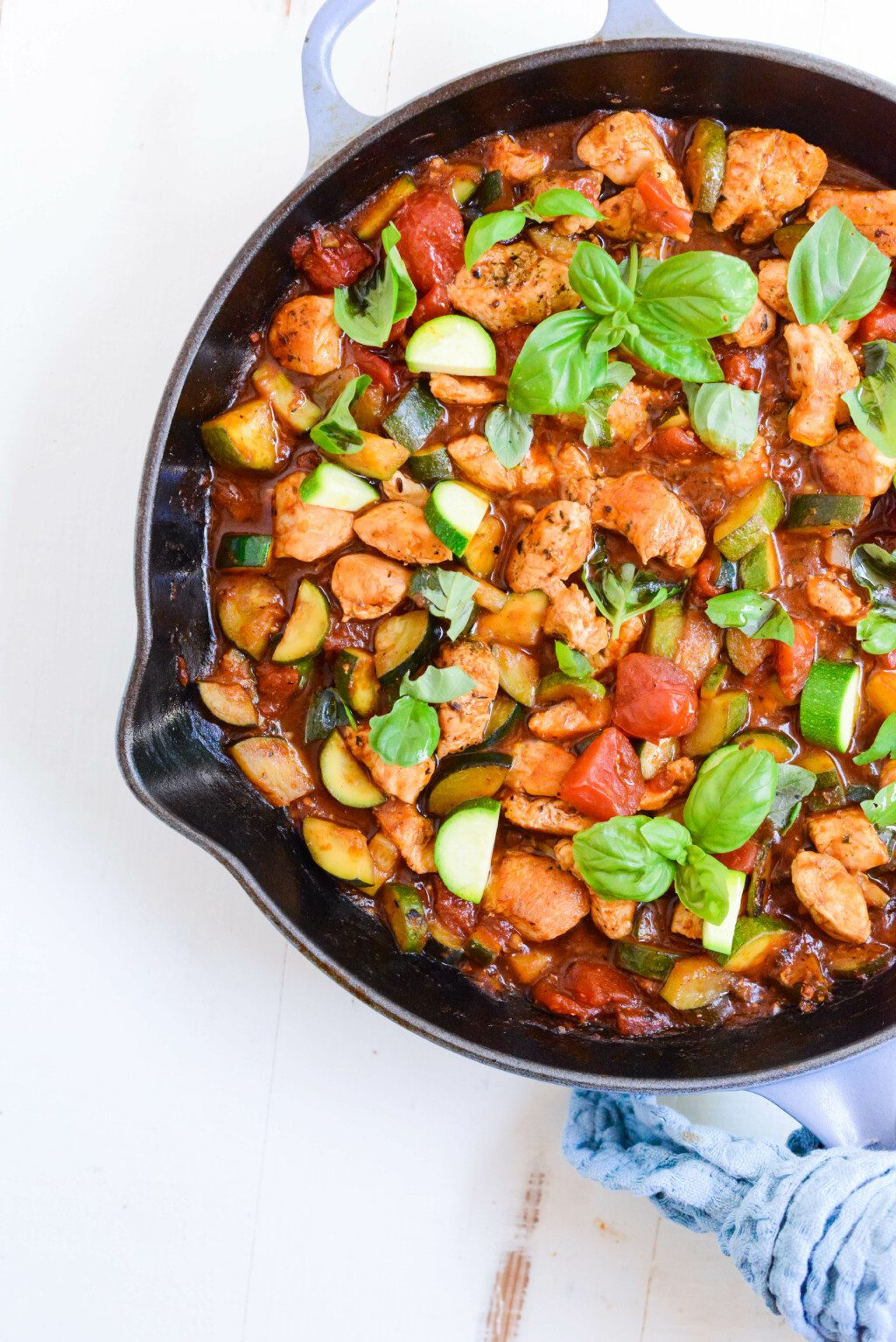 black pan with chicken and zucchini on white table