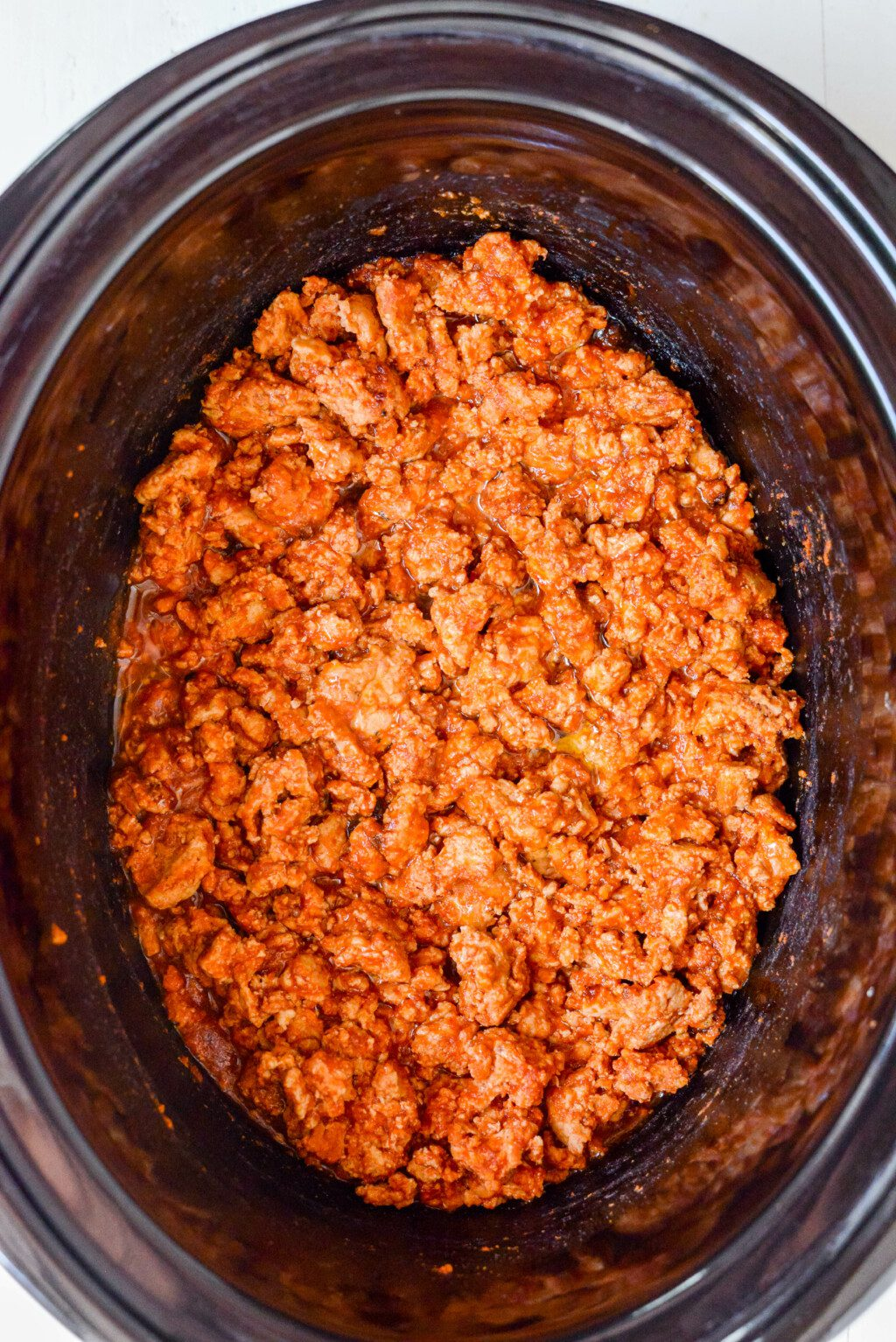 turkey taco meat in a black slow cooker on white table