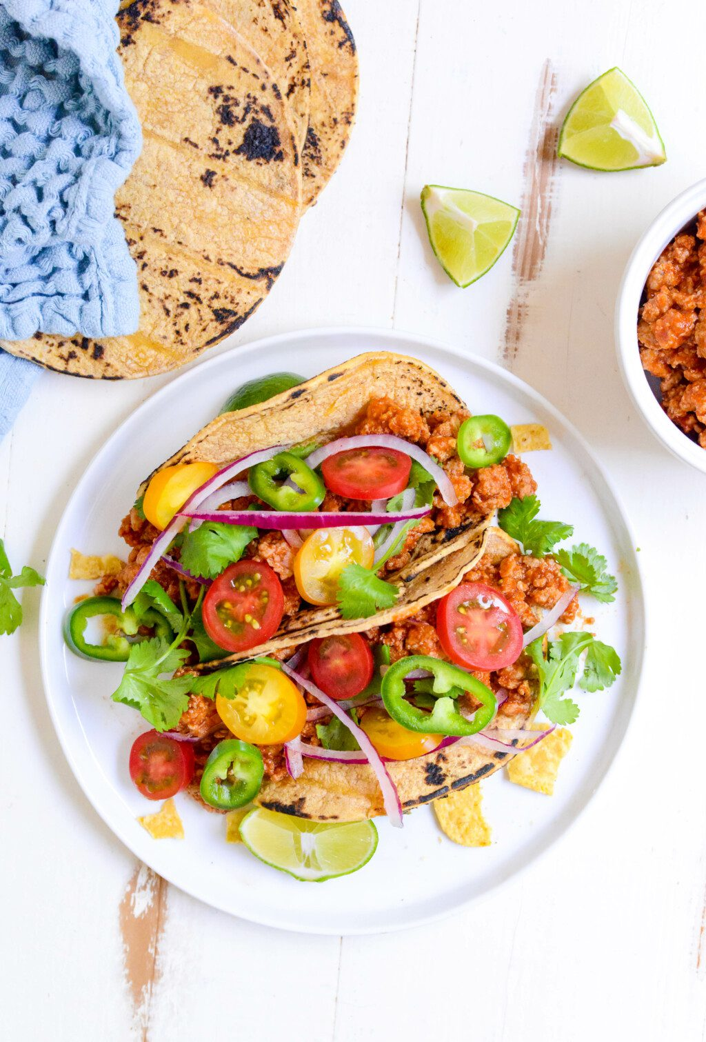 two slow cooker turkey tacos on a white plate with lime wedges and tortillas