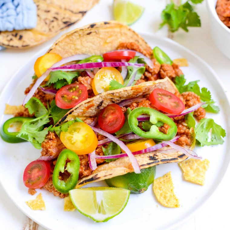 two slow cooker turkey tacos on a white plate with cilantro and lime wedges