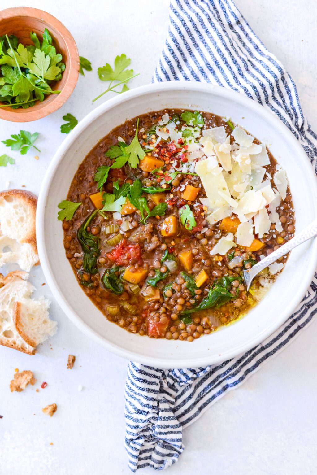 white bowl of crockpot lentil soup with fresh herbs and crusty bread on the side