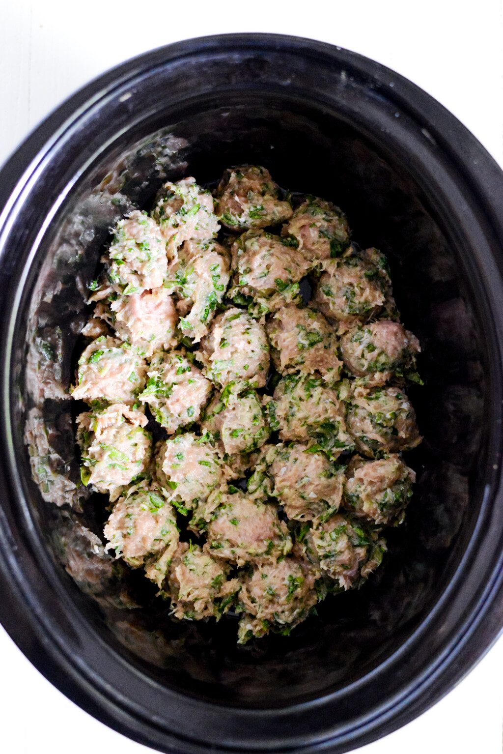 top down shot of crockpot turkey meatballs with herbs on top