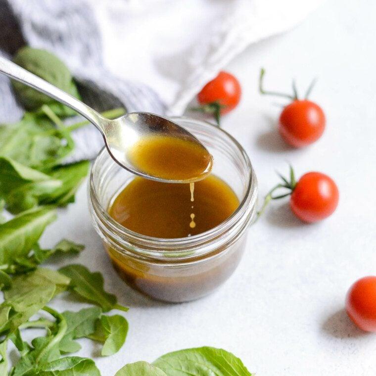 spoon full of easy balsamic vinaigrette dipping into a glass jar