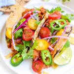 two instant pot turkey tacos on a white plate with cilantro and lime wedges