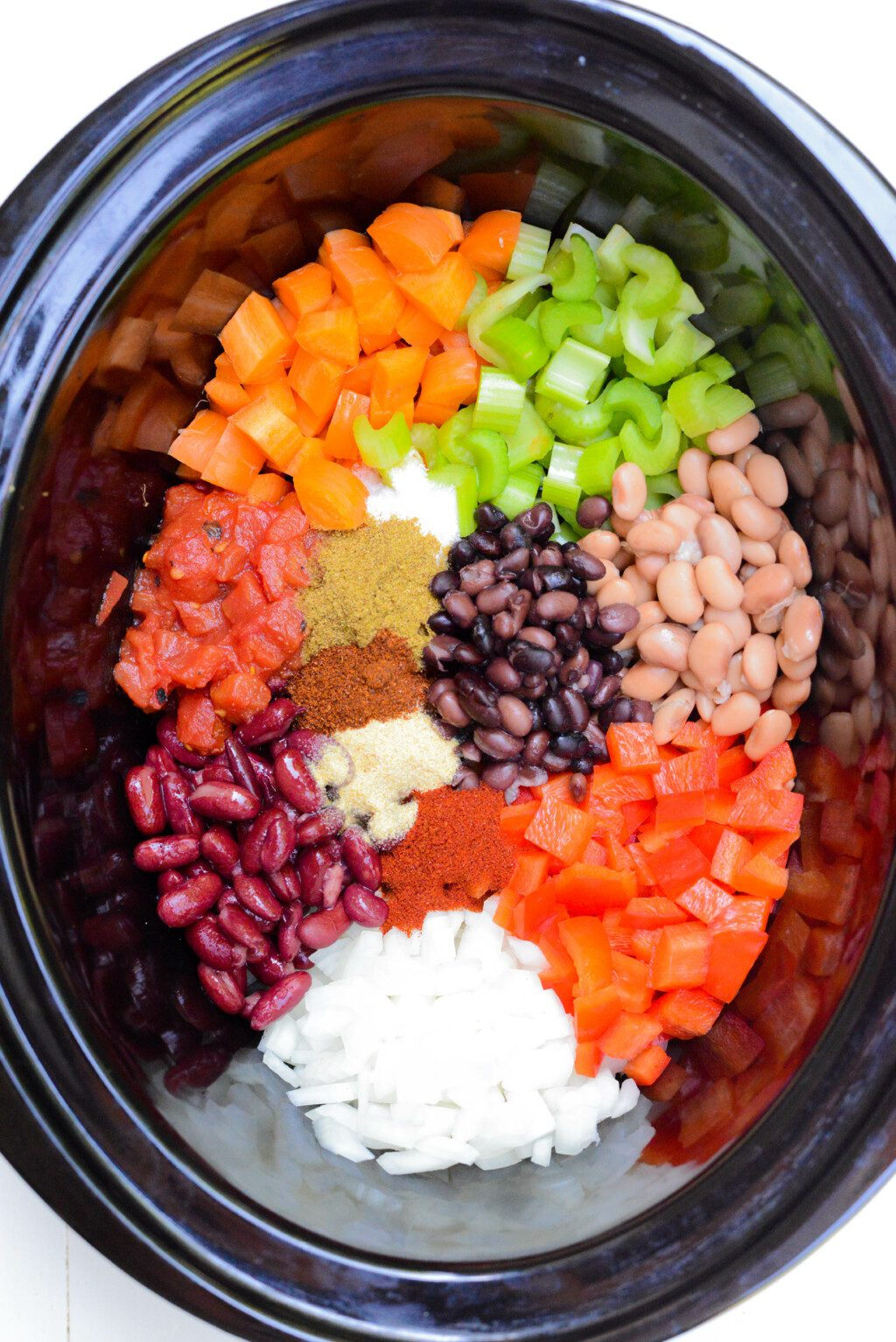 top down shot of beans and bell peppers and spices in a black slow cooker pot