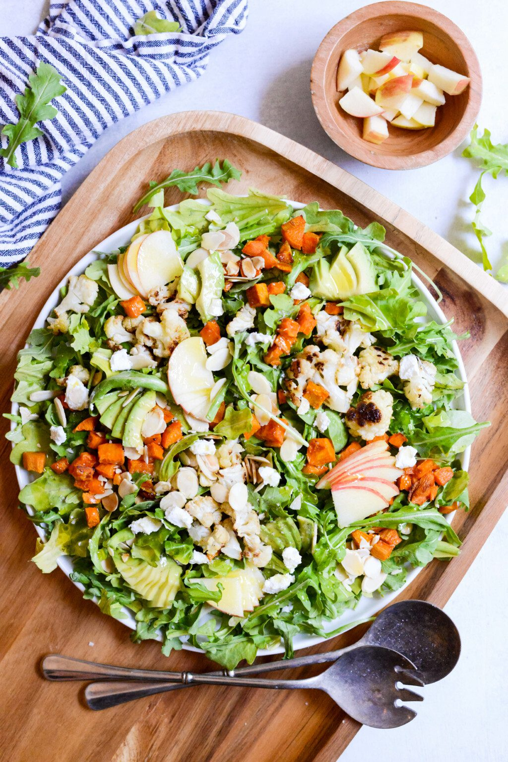 fall harvest salad on top of wood cutting board with striped napkin