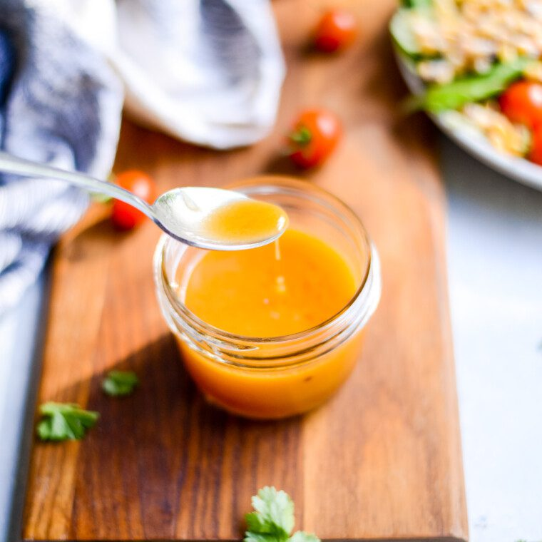 spoon dipping into a glass jar of salad dressing