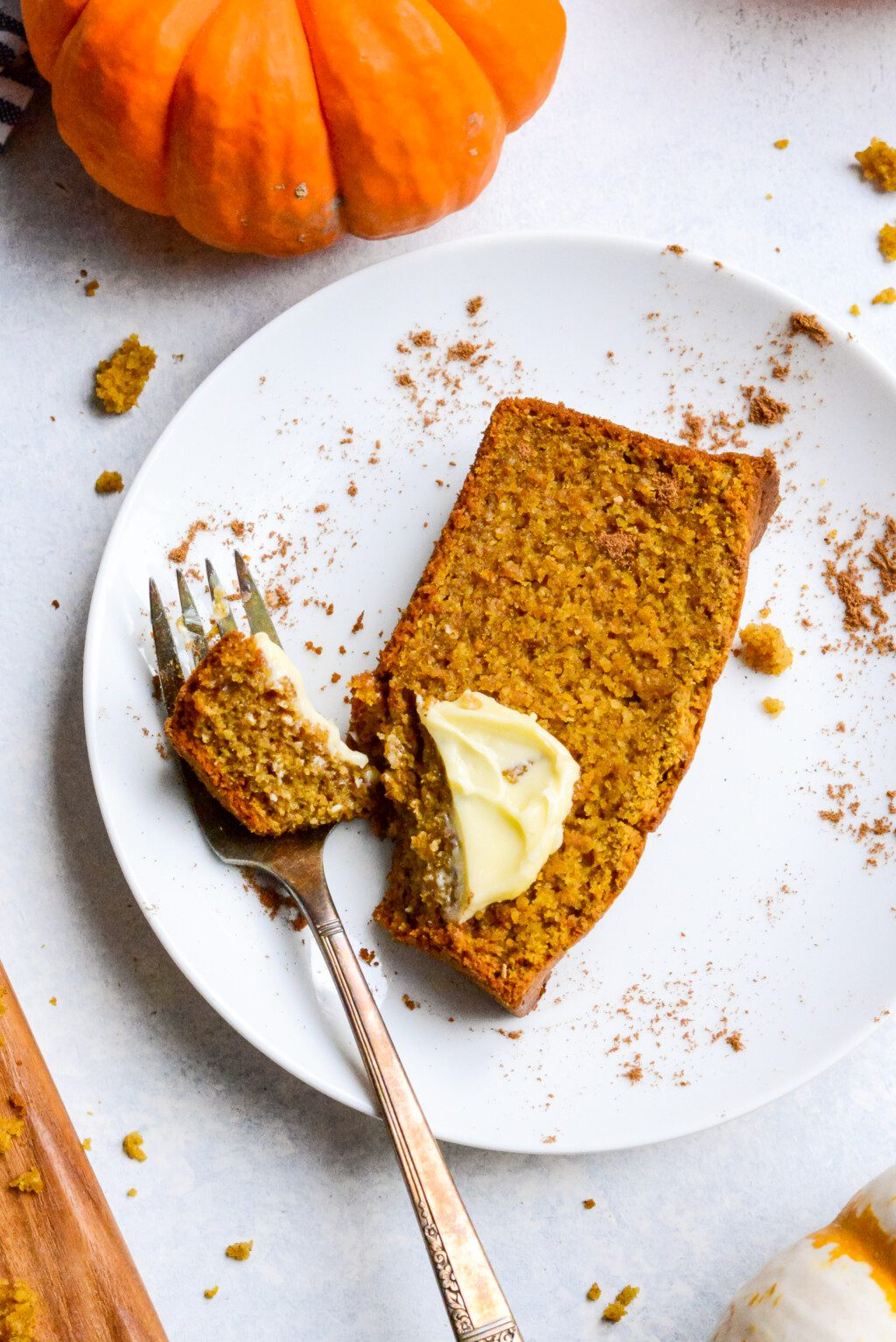 top down view of a slice of gluten free pumpkin bread with butter and cinnamon