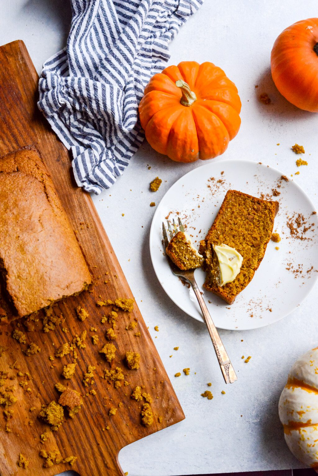 top down view of a slice of pumpkin bread on a white plate next to a loaf of bread